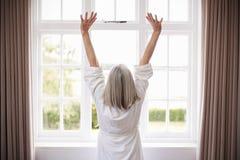 Οπισθοσκόπος του ανώτερου τεντώματος γυναικών μπροστά από το παράθυρο κρεβατοκάμαρων στοκ εικόνα