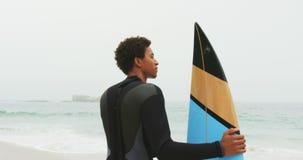 Οπισθοσκόπος του αρσενικού αφροαμερικάνων surfer που στέκεται με την ιστιοσανίδα στην παραλία 4k φιλμ μικρού μήκους