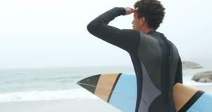 Οπισθοσκόπος του αρσενικού αφροαμερικάνων surfer που στέκεται με την ιστιοσανίδα στην παραλία 4k απόθεμα βίντεο