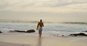 Οπισθοσκόπος του αρσενικού αφροαμερικάνων surfer που τρέχει με την ιστιοσανίδα στην παραλία 4k απόθεμα βίντεο