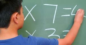 Οπισθοσκόπος του ασιατικού μαθητή που λύνει math το πρόβλημα στον πίνακα κιμωλίας στην τάξη στο σχολείο 4k φιλμ μικρού μήκους