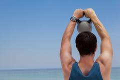 Οπισθοσκόπος του ατόμου που ανυψώνει kettlebell στην παραλία Στοκ φωτογραφία με δικαίωμα ελεύθερης χρήσης