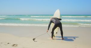 Οπισθοσκόπος του δραστήριου ανώτερου καυκάσιου αρσενικού surfer που στέκεται με την ιστιοσανίδα στην παραλία 4k φιλμ μικρού μήκους