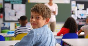 Οπισθοσκόπος του ευτυχούς καυκάσιου μαθητή που εξετάζει τη κάμερα στην τάξη 4k απόθεμα βίντεο