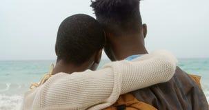 Οπισθοσκόπος του ζεύγους αφροαμερικάνων που αγκαλιάζει το ένα το άλλο στην παραλία 4k φιλμ μικρού μήκους