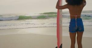 Οπισθοσκόπος του θηλυκού αφροαμερικάνων surfer που στέκεται με την ιστιοσανίδα στην παραλία 4k φιλμ μικρού μήκους