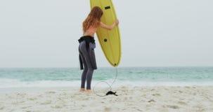 Οπισθοσκόπος του καυκάσιου θηλυκού surfer που στέκεται με την ιστιοσανίδα στην παραλία 4k απόθεμα βίντεο