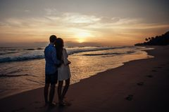 Οπισθοσκόπος του κοριτσιού και του αγοριού αγκαλιάστε ο ένας τον άλλον Νέο ζεύγος που απολαμβάνει το ηλιοβασίλεμα στην παραλία στ στοκ εικόνα