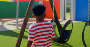 Οπισθοσκόπος του μαθητή αφροαμερικάνων που τρέχει προς την ταλάντευση στη σχολική παιδική χαρά 4k φιλμ μικρού μήκους