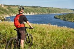 Οπισθοσκόπος του νέου ποδηλάτη στέκεται με το ποδήλατο βουνών στο πράσινο λιβάδι επάνω από το μεγάλο ποταμό Στοκ Εικόνες