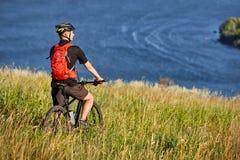 Οπισθοσκόπος του νέου ποδηλάτη στέκεται με το ποδήλατο βουνών στο πράσινο λιβάδι επάνω από το μεγάλο ποταμό Στοκ Φωτογραφία