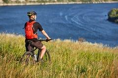 Οπισθοσκόπος του νέου ποδηλάτη στέκεται με το ποδήλατο βουνών στο πράσινο λιβάδι επάνω από το μεγάλο ποταμό Στοκ εικόνες με δικαίωμα ελεύθερης χρήσης