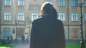 Οπισθοσκόπος του νέου σπουδαστή αφροαμερικάνων με τα dreadlocks που πηγαίνουν στο πανεπιστήμιο στην ηλιοφάνεια φιλμ μικρού μήκους