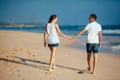 Οπισθοσκόπος του ρομαντικού ευτυχούς ζεύγους που περπατά σε ετοιμότητα εκμετάλλευσης παραλιών και εξετάστε ο ένας τον άλλον στο μ στοκ φωτογραφία με δικαίωμα ελεύθερης χρήσης