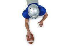 Οπισθοσκόπος του φορέα αμερικανικού ποδοσφαίρου που βρίσκεται στο μέτωπο με τη σφαίρα στοκ εικόνα