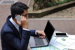 Οπισθοσκόπος του όμορφου νέου επιχειρηματία μιλά στο τηλέφωνο για την εργασία του στοκ εικόνες
