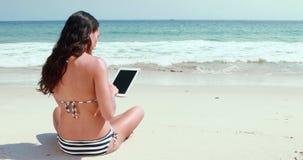 Οπισθοσκόπος του όμορφου brunette χρησιμοποιώντας το PC ταμπλετών στην παραλία απόθεμα βίντεο