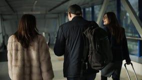 Οπισθοσκόπος τριών φίλων με τη βαλίτσα και των εγγράφων που περπατούν στο διάδρομο στο μπροστινό γραφείο απόθεμα βίντεο