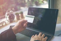 Οπισθοσκόπος των σύγχρονων χεριών επιχειρηματιών που κρατούν τους αριθμούς δακτυλογράφησης πιστωτικών καρτών στο πληκτρολόγιο υπο Στοκ Εικόνα