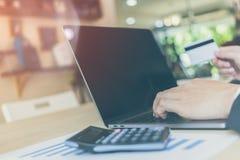 Οπισθοσκόπος των σύγχρονων χεριών επιχειρηματιών που κρατούν τους αριθμούς δακτυλογράφησης πιστωτικών καρτών στο πληκτρολόγιο υπο Στοκ Εικόνες