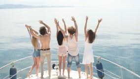 Οπισθοσκόπος των φίλων γιορτάστε sailboat στον ωκεανό, όπλα που αυξάνονται απόθεμα βίντεο