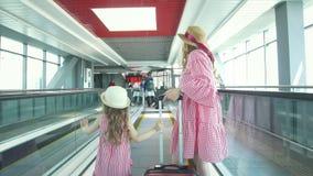 Οπισθοσκόπος των χεριών μητέρων και λίγης εκμετάλλευσης κορών που περπατούν στη αίθουσα αναμονής στον αερολιμένα απόθεμα βίντεο