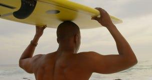 Οπισθοσκόπος φέρνοντας ιστιοσανίδας surfer αφροαμερικάνων της αρσενικής στο κεφάλι του στην παραλία 4k απόθεμα βίντεο