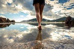 Οπισθοσκόπος φωτογραφία των όμορφων θηλυκών ποδιών που περπατούν στο νερό surfac Στοκ Εικόνες