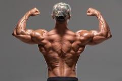 Οπισθοσκόπο μυϊκό άτομο που παρουσιάζει τους ραχιαίους μυς και δικέφαλους μυς, που απομονώνονται στο γκρίζο υπόβαθρο Ισχυρός αρσε στοκ φωτογραφία με δικαίωμα ελεύθερης χρήσης