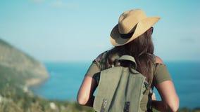 Οπισθοσκόπο ταξίδι απόλαυσης backpacker θηλυκό που πλησιάζει στην όμορφη θάλασσα που περιβάλλεται από τα βουνά απόθεμα βίντεο