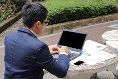 Οπισθοσκόπο της όμορφης νέας επιχείρησης το άτομο δακτυλογραφεί στο lap-top ενάντια στο smartphone και τα έγγραφα σχετικά με το τ στοκ εικόνες