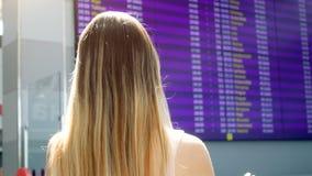 Οπισθοσκόπο 4k βίντεο της νέας γυναίκας με τη μακρυμάλλη εξέταση την επίδειξη με το χρόνο των αναχωρήσεων αεροσκαφών σε διεθνή φιλμ μικρού μήκους