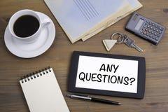 Οποιεσδήποτε ερωτήσεις; Κείμενο στη συσκευή ταμπλετών σε έναν ξύλινο πίνακα Στοκ Εικόνες