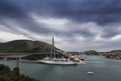 Οπτική παραίσθηση, μεγάλο σκάφος τουριστών κάτω από το διάσημο bridgre κοντά σε Dubrovnik, Κροατία Στοκ Εικόνες