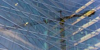 Οπτική παραίσθηση του γερανού συνταγμάτων που παγιδεύεται μέσα στο κτήριο γυαλιού Στοκ Εικόνες