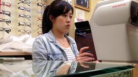 Οπτικός γυναικών που εξετάζει το αρσενικό όραμα ματιών απόθεμα βίντεο
