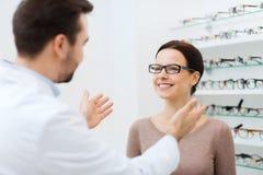 Οπτικός και γυναίκα στα γυαλιά στο κατάστημα οπτικής στοκ εικόνες με δικαίωμα ελεύθερης χρήσης