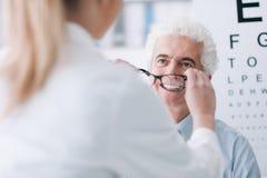 Οπτικός που δίνει τα νέα γυαλιά στον ασθενή στοκ φωτογραφία με δικαίωμα ελεύθερης χρήσης