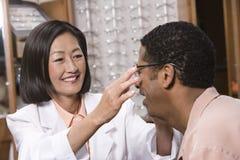 Οπτικός που βοηθά τον αρσενικό ασθενή στοκ φωτογραφία