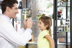 Οπτικός που βοηθά το κορίτσι για να επιλέξει τα γυαλιά στοκ εικόνα