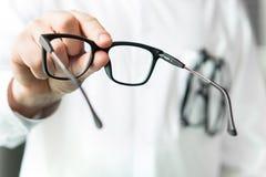 Οπτικός που δίνει τα νέα γυαλιά στον πελάτη για τη δοκιμή και την προσπάθεια στοκ εικόνες