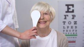 Οπτικός που κλείνει το ηλικιωμένο γυναικείο μάτι, που διατηρεί την ικανοποιητική όραση, δοκιμή απόθεμα βίντεο