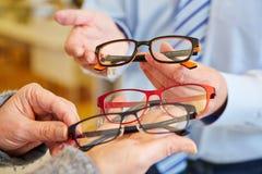 Οπτικός που προσφέρει την επιλογή των γυαλιών στοκ φωτογραφίες