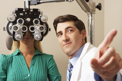 Οπτικός στη χειρουργική επέμβαση που δίνει τη δοκιμή ματιών γυναικών στοκ εικόνα