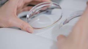 Οπτικός στρογγυλός φακός στα θηλυκά χέρια επιθεώρηση απόθεμα βίντεο