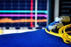 Οπτικών ινών καλώδιο με το φάσμα analiser στο υπόβαθρο Στοκ Φωτογραφία