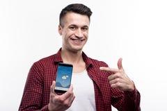 Οπτιμιστές άτομο που δείχνει στο τηλέφωνο με τον καιρό app Στοκ Εικόνες