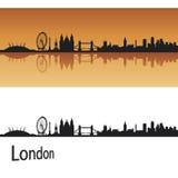 Ορίζοντας του Λονδίνου στην πορτοκαλιά ανασκόπηση Στοκ Φωτογραφίες