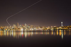Ορίζοντας του Σιάτλ τή νύχτα με το ίχνος αεροπλάνων Στοκ Εικόνα