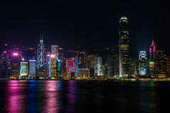 Ορίζοντας Χονγκ Κονγκ τη νύχτα από πέρα από το λιμάνι Στοκ Εικόνες